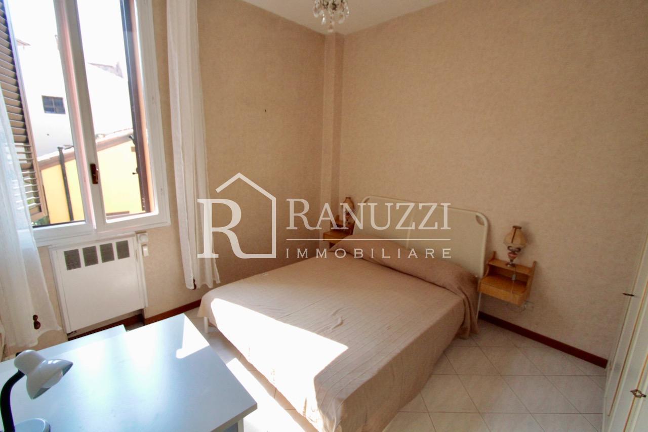 Battisti_grande bilocale_camera da letto con ampia finestra vista sui tetti